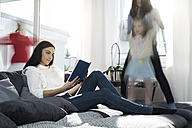 Girls jumping on sofa while mother reading a book - SBOF00662