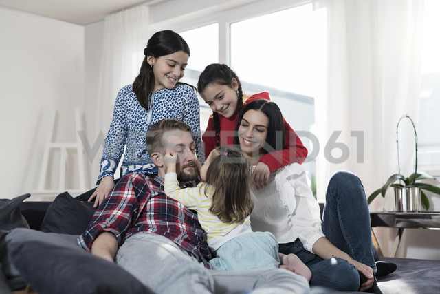 Parents and three daughers on sofa in living room - SBOF00665 - Steve Brookland/Westend61