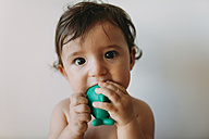 Portrait of baby girl biting a plastic toy - GEMF01792