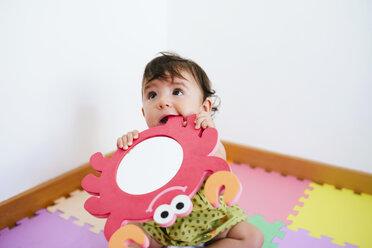 Cute baby girl biting a foam crab toy - GEMF01801