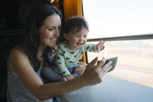 Happy mother and baby girl using smartphone while traveling by train - GEMF01807