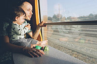 Father and baby girl traveling by train looking out of window - GEMF01813
