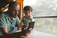 Father holding his baby girl and using smartphone while traveling by train - GEMF01816