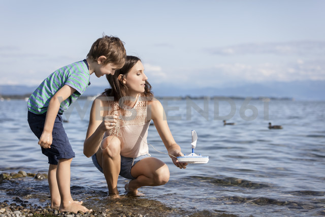 Germany, Friedrichshafen, Lake Constance, mother and son with toy boat at lakeshore - MIDF00862 - Miriam Dörr/Westend61