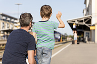 Son with father waving to mother on platform - MIDF00871