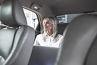 Businesswoman with laptop in car - VPIF00039
