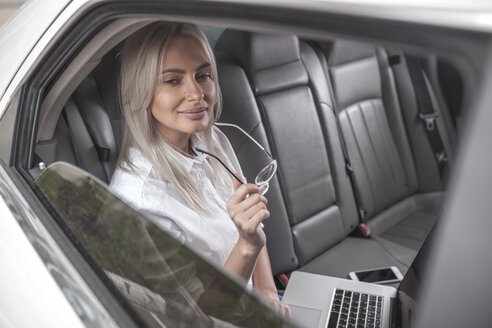 Smiling businesswoman with glasses using laptop in car - VPIF00042