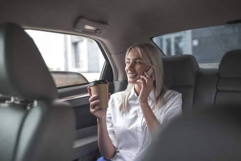 Smiling businesswoman with takeaway coffee on cell phone in car - VPIF00045