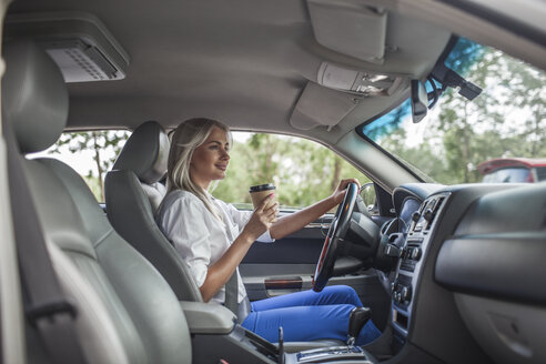 Smiling businesswoman holding takeaway coffee driving car - VPIF00048