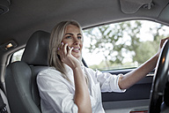 Smiling businesswoman on cell phone driving car - VPIF00051