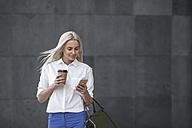 Smiling businesswoman with takeaway coffee and cell phone on the move - VPIF00054