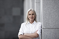 Portait of confident businesswoman leaning against a wall - VPIF00060