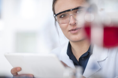Scientist working in lab holding a tablet looking at flask - ZEF14596