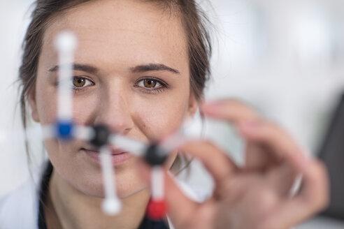 Scientist working in lab holding molecular structure - ZEF14599