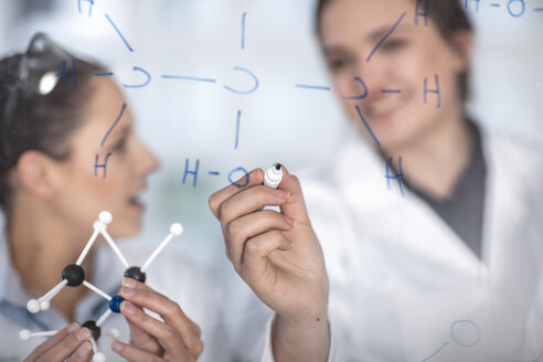 Two scientists working in lab writing notes on glass pane - ZEF14602