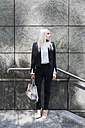 Young businesswoman standing outdoors looking around - GIOF03186