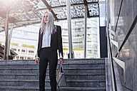 Young businesswoman standing on stairs in the city - GIOF03189