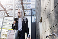 Young businesswoman checking cell phone in the city - GIOF03192