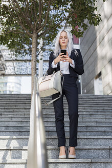 Young businesswoman checking cell phone on stairs in the city - GIOF03195