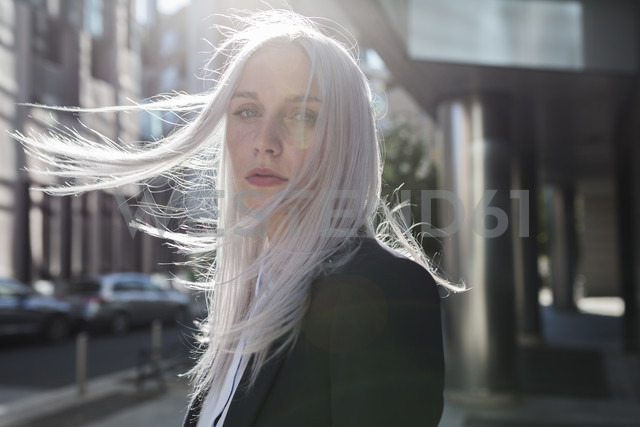 Portrait of young businesswoman with windswept hair in the city - GIOF03201