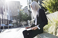 Young businesswoman sitting on a wall in the city using laptop - GIOF03204