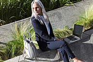 Young businesswoman sitting on a wall in the city using laptop - GIOF03210