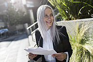 Smiling young businesswoman sitting on a wall in the city with documents - GIOF03213