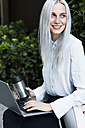 Smiling young businesswoman sitting on a wall with coffee mug and laptop - GIOF03225