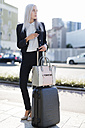 Young businesswoman in the city with cell phone and luggage - GIOF03231