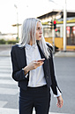 Young businesswoman in the city with cell phone looking around - GIOF03237