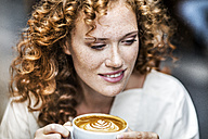 Portrait of smiling young woman with Cappuccino - FMKF04479