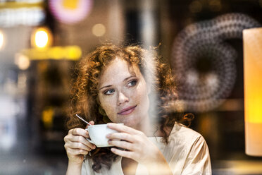 Portrait of smiling young woman with coffee cup behind windowpane of a coffee shop - FMKF04482