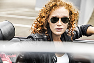 Portrait of redheaded woman wearing sunglasses in sports car - FMKF04496