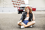 Portrait of confident redheaded woman sitting on parking level - FMKF04499