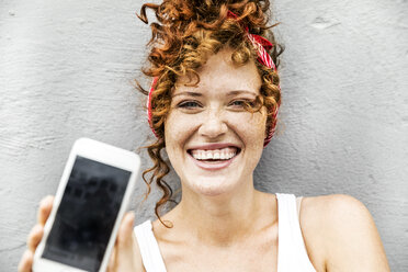 Happy redheaded woman showing cell phone - FMKF04508