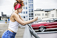 Redheaded woman on parking level holding cell phone - FMKF04511