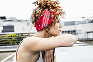 Serious redheaded woman leaning on wall - FMKF04514