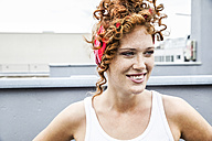 Portrait of smiling redheaded woman outdoors - FMKF04517
