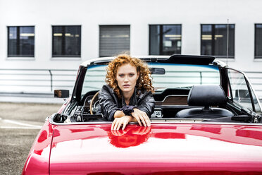 Portrait of confident redheaded woman in sports car - FMKF04520