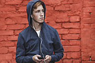 Young man with cell phone and earphones at red brick wall - VPIF00084
