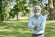 Portrait of smiling mature man with beard and glasses outdoors - JOSF01697