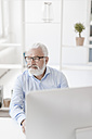 Smiling mature man with beard and glasses at desk - JOSF01703