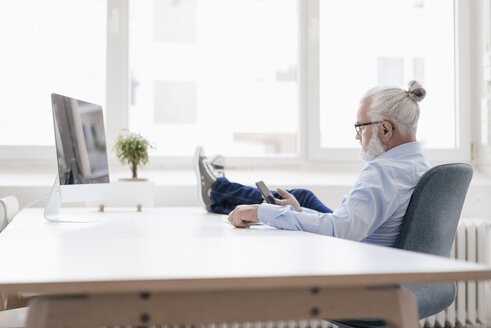 Mature man with beard using cell phone at desk - JOSF01706