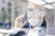 Mature man on cell phone behind windowpane - JOSF01715