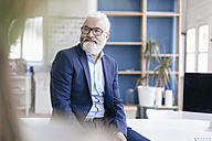 Confident mature man with beard and glasses in office - JOSF01718