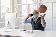 Mature man on cell phone at desk playing with basketball - JOSF01724