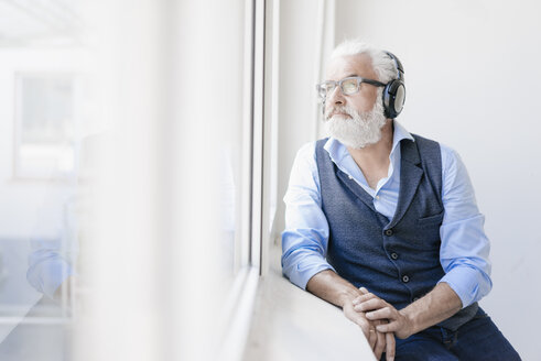 Mature man wearing glasses and headphones looking out of window - JOSF01727