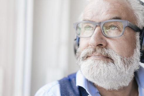 Mature man wearing glasses and headphones at the window - JOSF01730