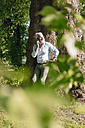 Smiling mature man on cell phone leaning against tree - JOSF01739