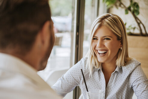 Happy young woman looking at man in a cafe - ZEDF00850